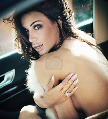 Perfect brunette beauty in a car