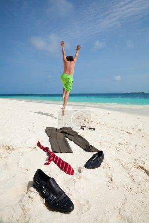 Photo pour Homme d'affaires heureux courant dans l'océan pour nager avec des vêtements tels que des bottes, cravate et pantalon enlevés et couchés sur le sable blanc - image libre de droit