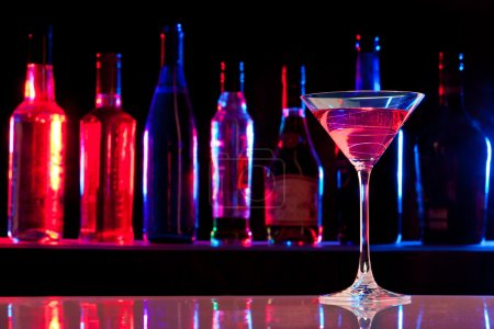 Photo for Cocktail glass with drink in the bar with bottles in the dark background - Royalty Free Image