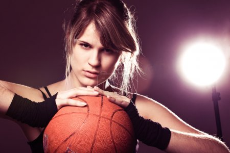Female basketball player holding ball