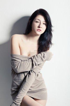 Woman posing at studio near wall, looking at camera
