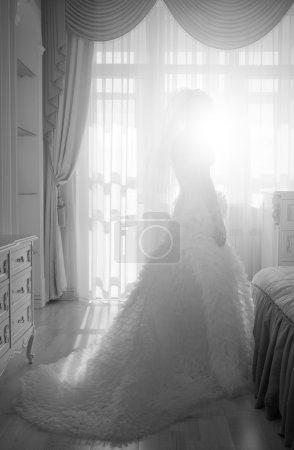 Foto de Hermosa novia con el vestido de boda preciosa parado junto a la ventana de la habitación - Imagen libre de derechos