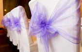 White wedding chairs decorated with purple bows