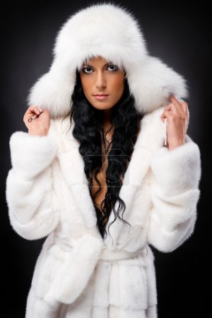 Beautiful woman in white fur coat and cap