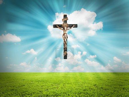 Photo for Jesus Christ on cross radiates light in sky over landscape - Royalty Free Image