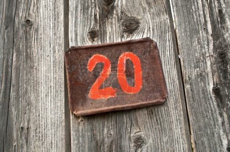 Photo for Number twenty on metal plate attached to wooden background - Royalty Free Image