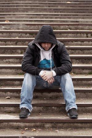 Photo for Sad teenage boy with hood sitting on stairs - Royalty Free Image