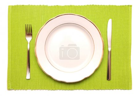 Knife, fork and white plate on a green napkin