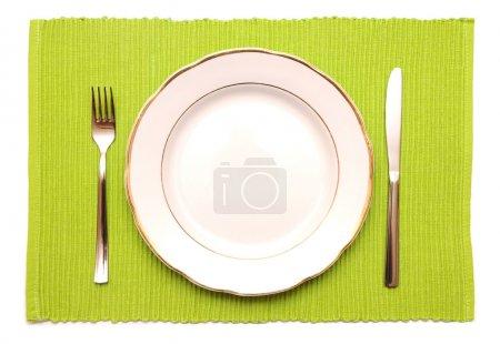 Foto de La placa de cuchillo, tenedor y blanco sobre una servilleta verde sobre un fondo blanco - Imagen libre de derechos