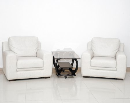 Photo for Detail of a modern living room with white armchair and glass coffee table - Royalty Free Image