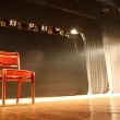 Red chair on empty stage lighted with spotlights...