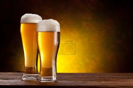 Photo pour Deux verres de bières sur une table en bois. fond jaune foncé - image libre de droit