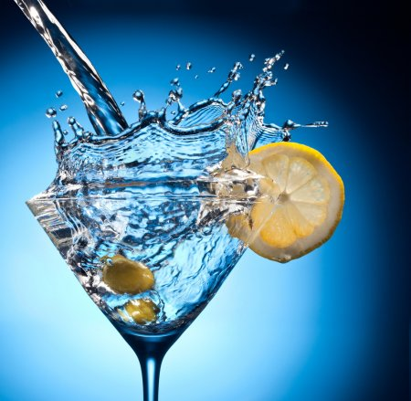 Photo for Splash from pouring martini into the glass. Object on a blue background. - Royalty Free Image