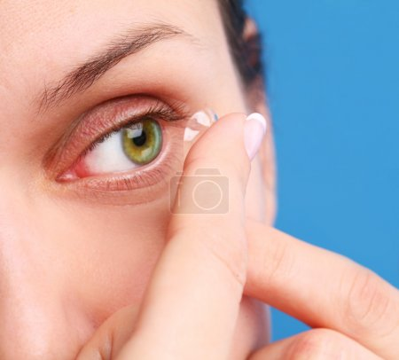 Human eye with corrective lens on a blue background