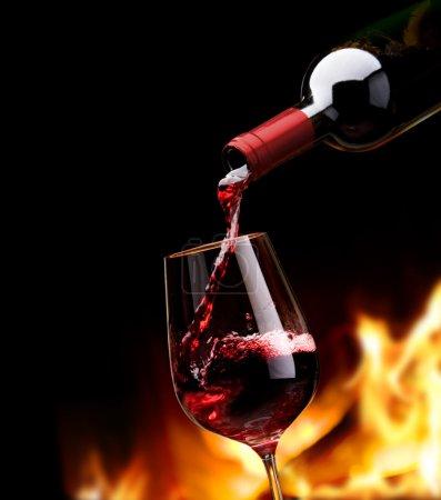 Foto de Verter el vino tinto de una botella en copa de vino - Imagen libre de derechos