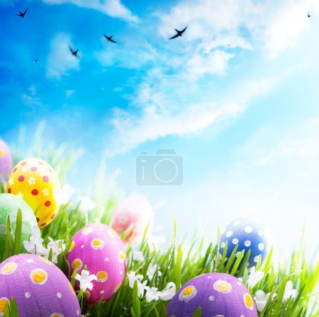 Art Easter eggs decorated with flowers in the grass on blue sky