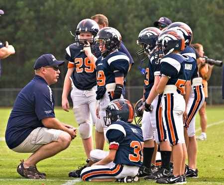 Photo for A coach talking to the players on a Youth League football team. - Royalty Free Image