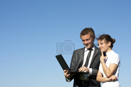 Two successful workers in the street with a laptop