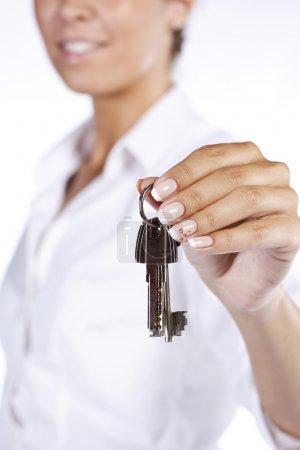 Main tenant deux clés de maison sur un porte-clés