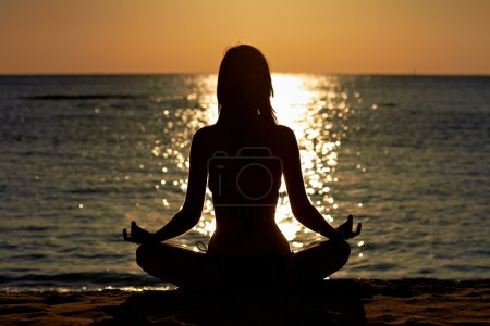 Photo for Silhouette of woman in yoga lotus meditation position front to seaside - Royalty Free Image