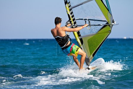Rear view of man windsurfing in splashes of water...