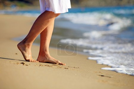 Photo for Cropped image of a young caucasian woman walking on a beach - Royalty Free Image