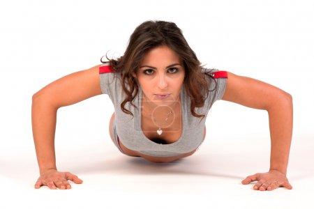 Attractive young woman doing pushups over white background