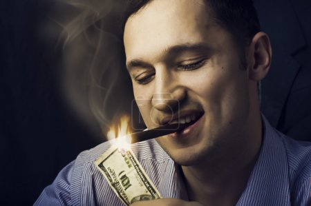 Man lighting his cigar with 100 dollars note