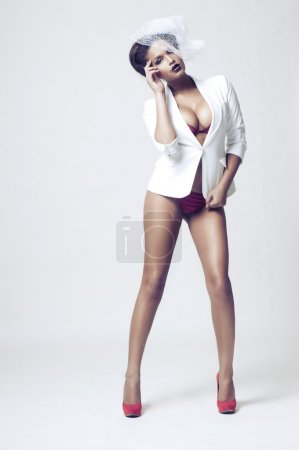 Sexy african woman posing in lingerie on light grey background