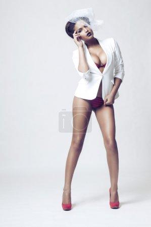 Photo pour Femme africaine sexy posant en lingerie sur fond gris clair - image libre de droit
