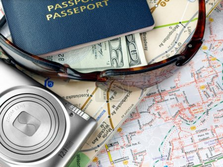Photo for Travel necessities: sunglasses, passports camera, dollars on the map - Royalty Free Image