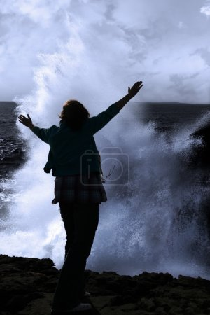Silhouette of lone woman facing a powerful wave on cliff edge