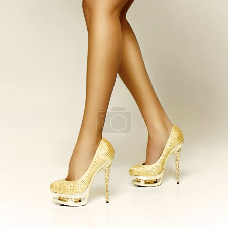 Photo for Sexy gold girl shoes, long sexy legs - Royalty Free Image