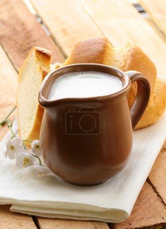 Pitcher of milk on a wooden table, rustic still li...