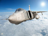 Military jet bomber Su-24 Fencer flying above the clouds.