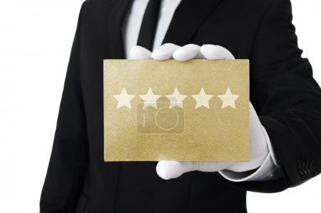 Photo for Elegant man holding gold card with five stars on it - Royalty Free Image