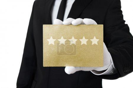 Foto de Hombre elegante aguantando tarjeta dorada con cinco estrellas - Imagen libre de derechos