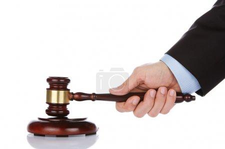 Human hand holding a gavel