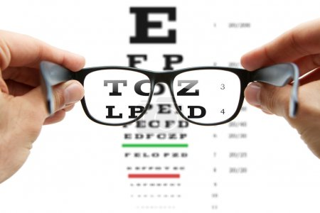 Photo for Human hands holding eyeglasses with eye chart in the back - Royalty Free Image