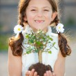 Girl holding tree as invironmental or nature conce...
