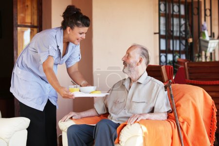Photo for Elderly senior being brought meal by carer or nurse - Royalty Free Image