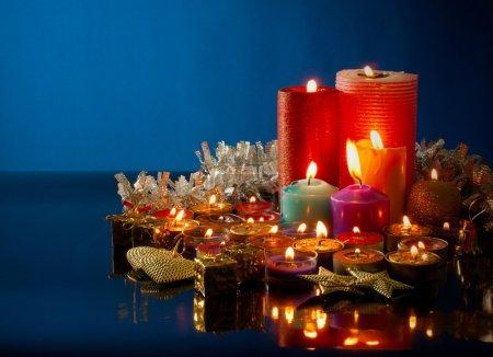 Photo pour Beaucoup de bougies colorées brûlantes sur fond bleu foncé - image libre de droit