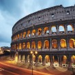 Coliseum at night with colorful blurred traffic li...