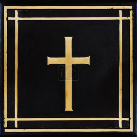 Golden cross, symbol of the Christian faith on the black backgro