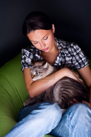 Happy young woman with cat, relaxed on the beanbag couch.