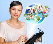 Portrait of young woman holding her tablet computer and communicating with her friends across the world. Standing against world map with photo of . International communications concept