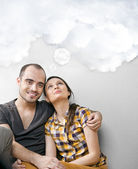 Attractive young adult couple sitting close on floor in home smi