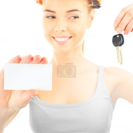 Photo for Happy woman wearing protective helmet holding new key and blank white card - Royalty Free Image