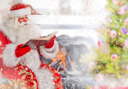 Photo for Santa sitting at the Christmas tree, near fireplace and reading a book. Indoors. Magic snowy poster - Royalty Free Image