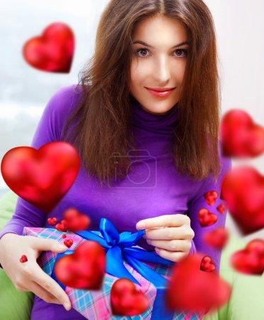 Photo pour Femme ravie ouvrant son cadeau tout en étant assise sur le sac de haricots à la maison et de belles formes de coeur rouge volent autour . - image libre de droit